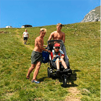 Andres and his brother helping him to mount the mountains in the european alpes in his Delta Push chair