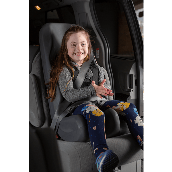 A girl enjoying sitting in the comfortable booster car seat.